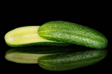 Group of two halves of fresh green pickling cucumber one sliced isolated on black glass