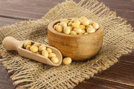 Beaucoup de graines de soja jaunes crues entières dans un bol en bois avec une cuillère en bois sur un tissu de jute sur du bois marron