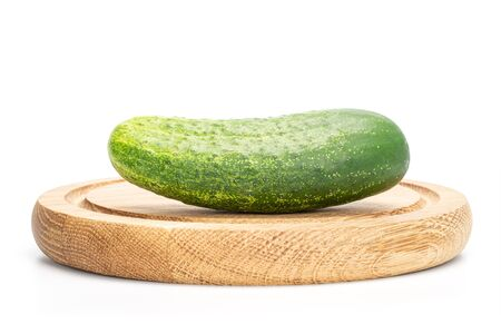One whole fresh green pickling cucumber on bamboo plate isolated on white background