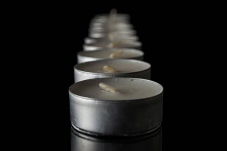 Lot of whole waxy white tea candle in row isolated on black glass