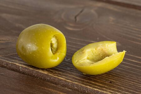 Group of one whole one half of pitted green olive on brown wood