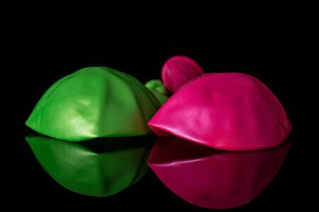 Group of two whole latex pastel ballon isolated on black glass