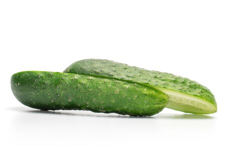 Group of two halves of fresh pickling cucumber one sliced isolated on white background