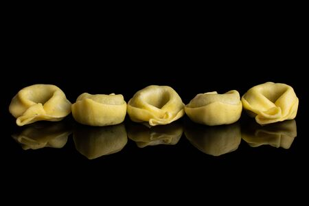 Group of five whole fresh yellow spinach filled tortelloni isolated on black glass