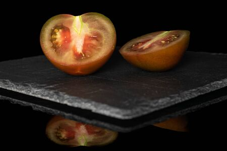 Group of two halves of fresh green red tomato on grey stone isolated on black glass