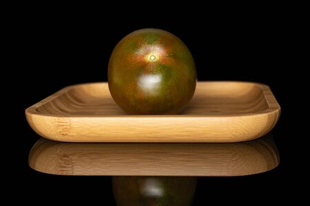 One whole fresh green red tomato on wooden square plate isolated on black glass Stock Photo
