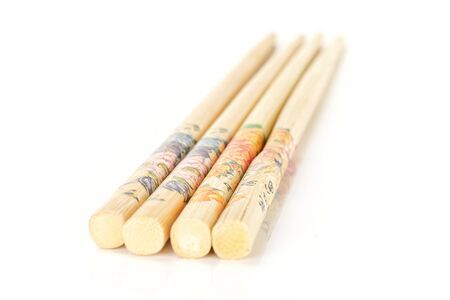 Group of four whole asian brown chopsticks in row isolated on white background