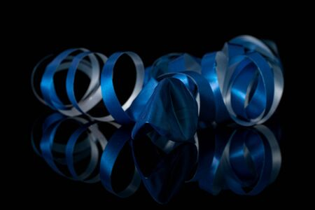 One whole blue ribbon isolated on black glass