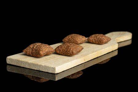 Group of four whole crispy brown cereal pillow on small wooden cutting board isolated on black glass