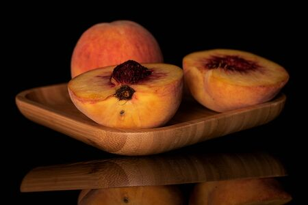 Group of one whole two halves of fresh fuzzy peach on wooden square plate isolated on black glass