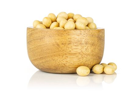 Lot of whole raw yellow soya bean in wooden bowl isolated on white background Stock Photo