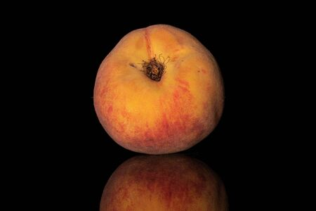 One whole fresh fuzzy peach isolated on black glass
