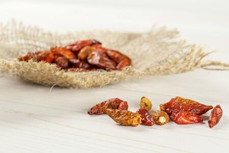 Lot of whole dry red chili pepper peperoncino on jute cloth on white wood
