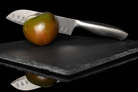 One whole fresh green red tomato on grey stone with santoku knife isolated on black glass