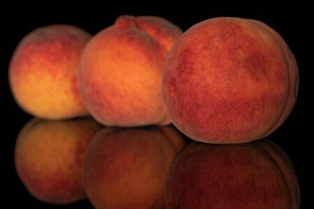 Group of three whole fresh fuzzy peach in row isolated on black glass