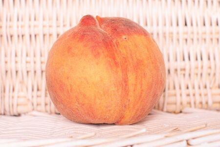 One whole bright fresh fuzzy peach with braided rattan behind
