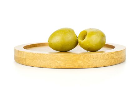 Group of two whole pitted green olive on bamboo plate isolated on white background