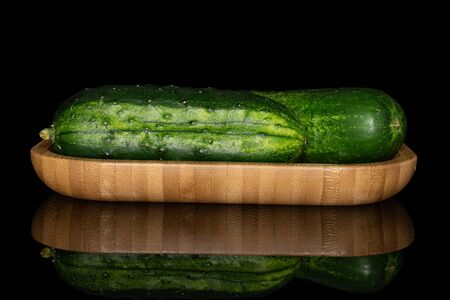Group of two whole fresh green pickling cucumber on wooden square plate isolated on black glass 스톡 콘텐츠
