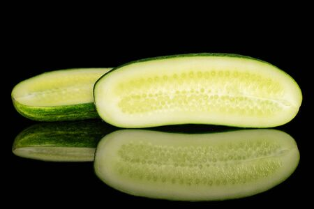 Group of two halves of fresh green pickling cucumber section isolated on black glass