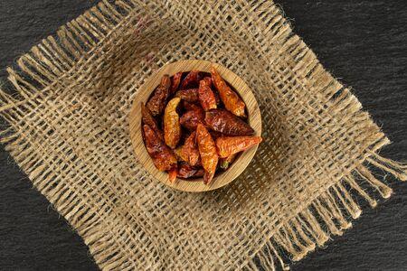 Beaucoup de peperoncino de piment rouge sec entier dans un bol en bois sur un plat en toile de jute sur une pierre grise Banque d'images