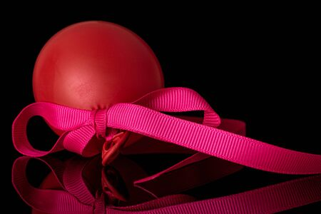 One whole red latex pastel ballon with pink ribbon isolated on black glass