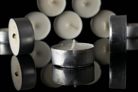 Lot of whole waxy white tea candle front focus isolated on black glass Stock Photo