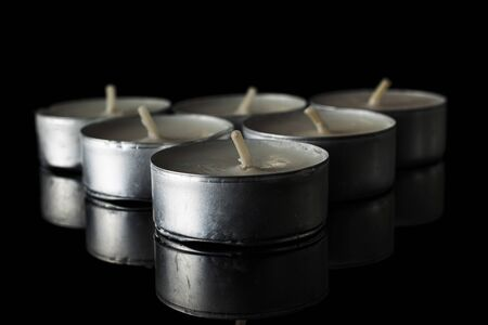 Group of seven whole waxy white tea candle isolated on black glass