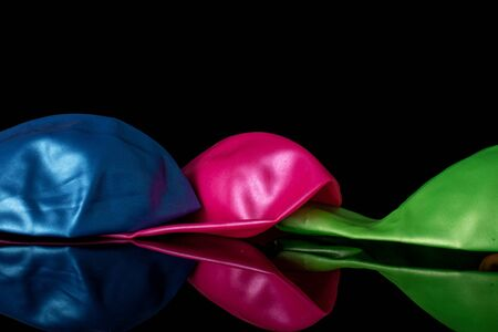 Group of three whole latex pastel ballon isolated on black glass