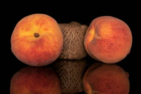 Group of two whole fresh fuzzy peach with spool isolated on black glass