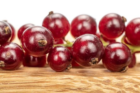 Lot of whole fresh dark redcurrant closeup on wooden square plate isolated on white background Stock Photo