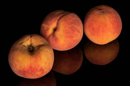 Group of three whole bright fresh fuzzy peach isolated on black glass