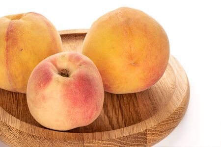 Group of three whole fresh fuzzy peach on bamboo plate isolated on white background