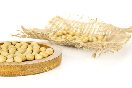 Lot of whole raw yellow soya bean on bamboo plate on jute cloth isolated on white background Stock Photo