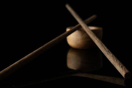 Group of two whole dark asian brown chopsticks crossed with wooden bowl isolated on black glass