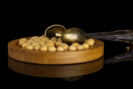 Lot of whole raw yellow soya bean on bamboo plate with sugar tongs isolated on black glass