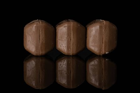 Group of six whole milk fresh chocolate piece in row isolated on black glass