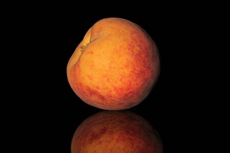 One whole bright fresh fuzzy peach isolated on black glass