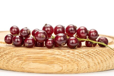Lot of whole fresh dark redcurrant on bamboo plate isolated on white background Stock Photo