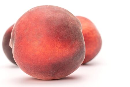 Group of three whole fresh fuzzy peach isolated on white background