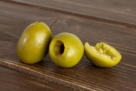 Group of two whole one half of pitted green olive on brown wood