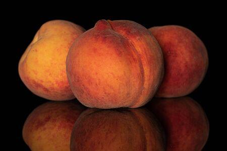 Group of three whole fresh fuzzy peach isolated on black glass Stok Fotoğraf