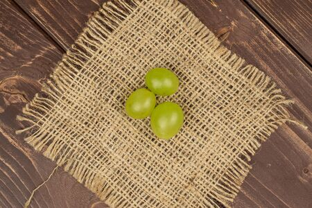 Group of three whole fresh green grape with jute fabric flatlay on brown wood