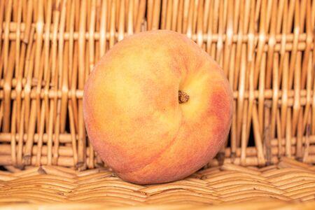 One whole fresh fuzzy peach with braided rattan behind Stok Fotoğraf