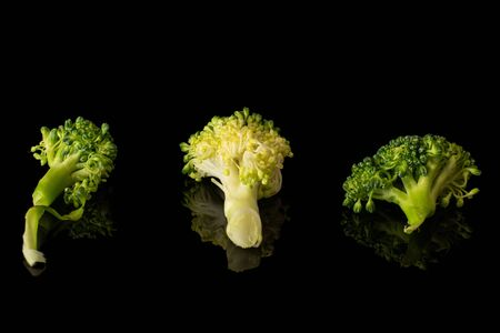 Group of three pieces of fresh green broccoli in row isolated on black glass