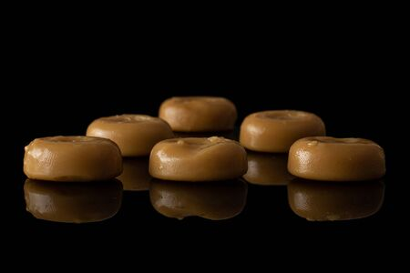 Lot of whole caramel brown candy isolated on black glass