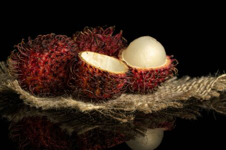 Group of two whole two halves of fresh red rambutan on jute cloth isolated on black glass
