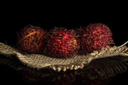 Groupe de trois ramboutan rouge frais entier sur toile de jute isolé sur verre noir