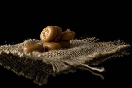 Lot of whole caramel brown candy with jute fabric isolated on black glass Stock Photo