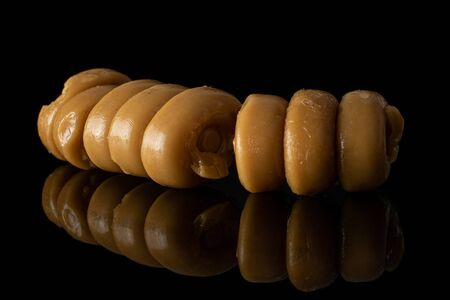 Lot of whole arranged caramel brown candy heap isolated on black glass Stock Photo