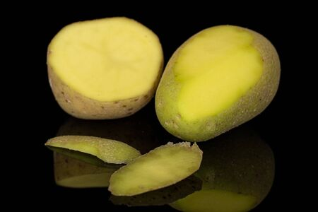 Group of one whole one half two pieces of raw brown potato isolated on black glass